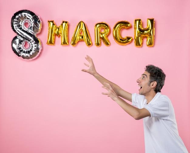 Vooraanzicht jonge man met maart decoratie op roze achtergrond vakantie glamour vrouwen dag feest vrouwelijke emoties kleur gelijkheid sensueel