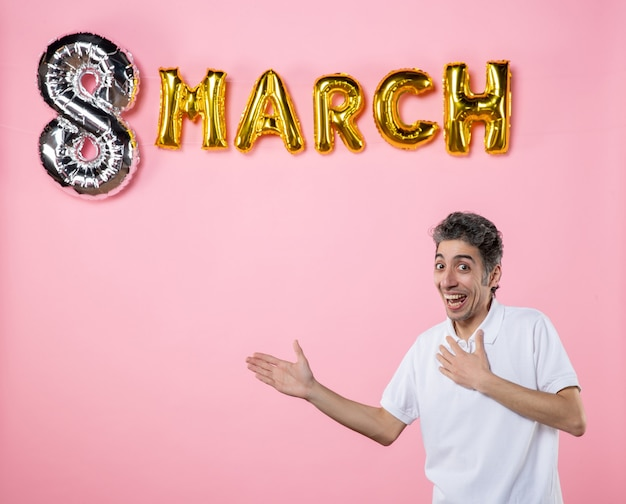 Vooraanzicht jonge man met maart decoratie op roze achtergrond vakantie glamour womens dag vrouwelijk sensueel feest kleur emotie