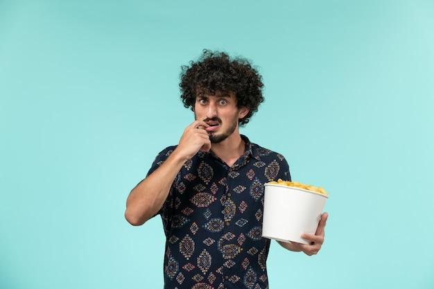 Vooraanzicht jonge man met mand met aardappel cips en kijken naar film op blauwe bureau mannelijke film bioscoop film afstandsbediening
