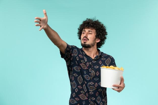 Vooraanzicht jonge man met mand met aardappel cips en kijken naar film op de blauwe muur mannelijke film bioscoop film afstandsbediening