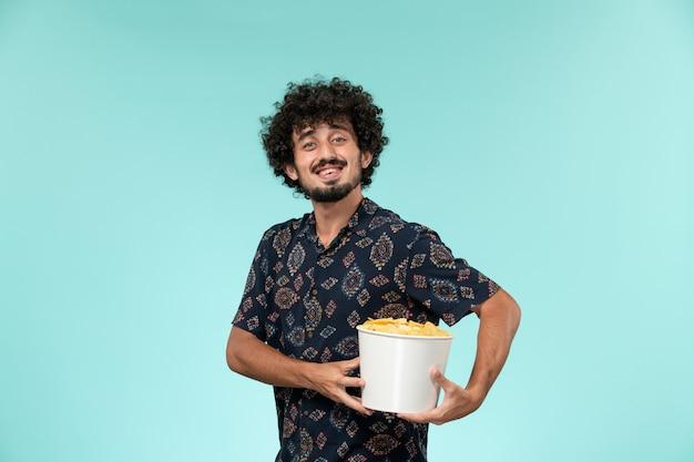 Vooraanzicht jonge man met mand met aardappel cips en lachend op een blauwe muur afgelegen film bioscoop bioscoop bioscoop
