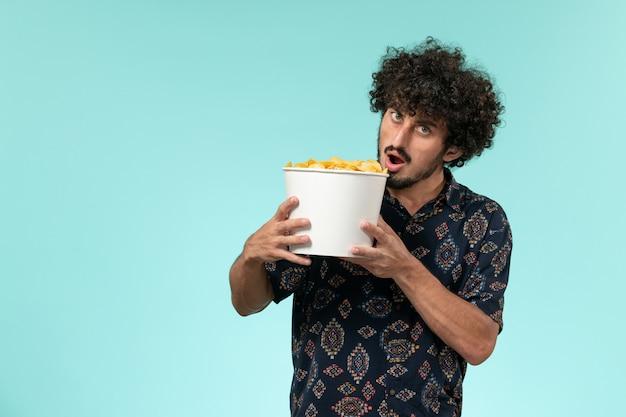 Vooraanzicht jonge man met mand met aardappel cips op de blauwe muur mannelijke film bioscoop film afstandsbediening