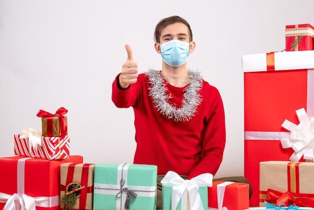 Vooraanzicht jonge man met masker duim omhoog teken rond xmas geschenken zitten