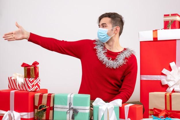 Vooraanzicht jonge man met masker geven hand rond xmas geschenken zitten