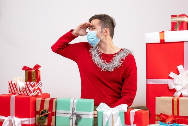 Vooraanzicht jonge man met masker kijken naar iets rond kerstcadeaus