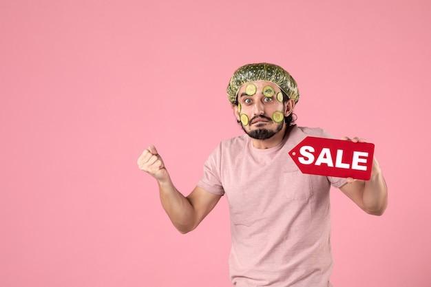 Vooraanzicht jonge man met masker op zijn gezicht met verkoop naamplaatje op roze achtergrond