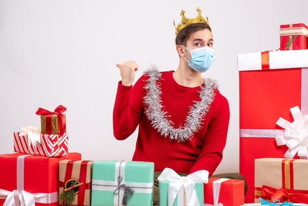 Vooraanzicht jonge man met masker wijzend op rug rond kerstcadeaus zitten