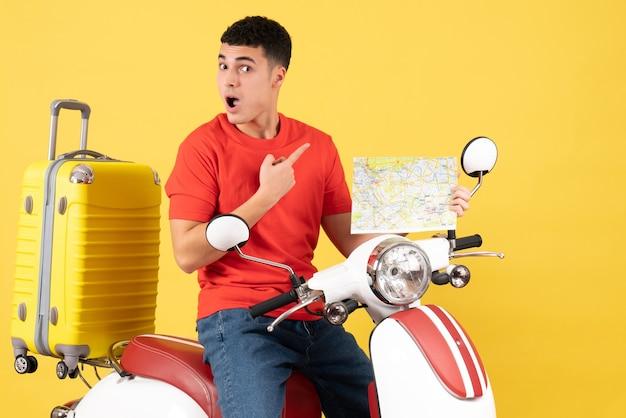 Vooraanzicht jonge man met nieuwsgierige blikken op bromfiets met reiskaart