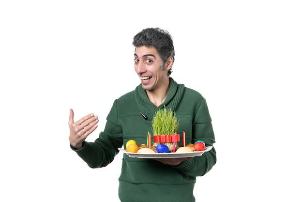 Vooraanzicht jonge man met novruz honca met snoep en semeni op witte achtergrond etniciteit performer kleuren concept etnische lente