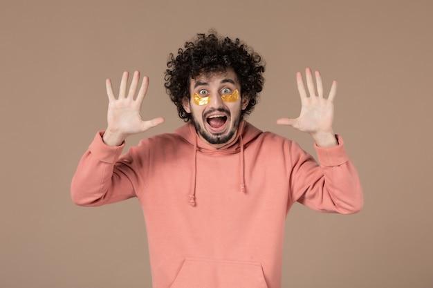 Vooraanzicht jonge man met ooglapjes op bruine achtergrond spa massage huidverzorging horizontale tijd huid schoonheid
