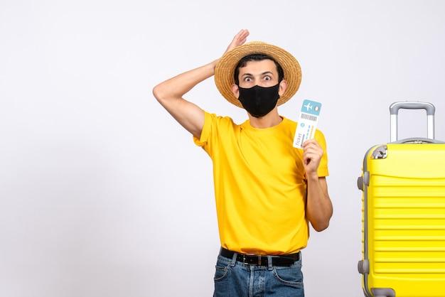 Vooraanzicht jonge man met open ogen met strooien hoed staande in de buurt van gele koffer met vliegticket