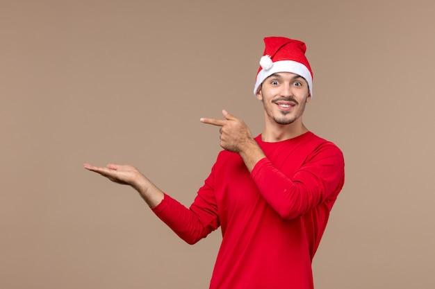 Vooraanzicht jonge man met opgewonden gezicht op bruine vloer emotie kerstvakantie
