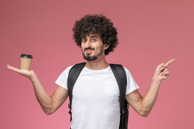 Vooraanzicht jonge man met papieren koffiekopje en wijst op de andere richting