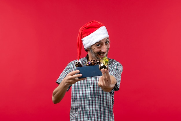 Vooraanzicht jonge man met plastic speelgoed op rode achtergrond