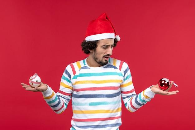 Vooraanzicht jonge man met plastic speelgoed op rode muur rode menselijke vakantie nieuwjaar