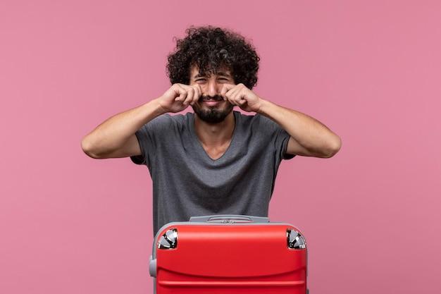 Vooraanzicht jonge man met rode tas die zich voorbereidt op een reis die huilt op roze ruimte
