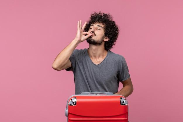 Vooraanzicht jonge man met rode tas die zich voordeed op roze bureau