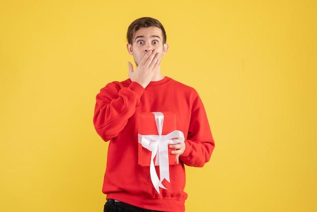 Vooraanzicht jonge man met rode trui voor zijn mond op gele achtergrond