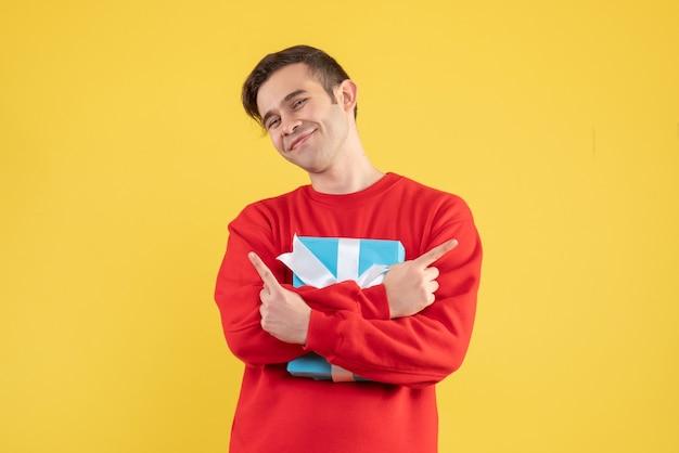 Vooraanzicht jonge man met rode trui zijn cadeau strak op gele achtergrond te houden
