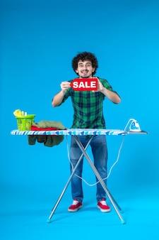 Vooraanzicht jonge man met rode verkoop schrijven op blauwe achtergrond huis mens wasmachine schoon huishoudelijk werk was