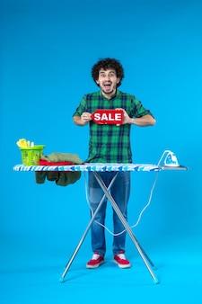 Vooraanzicht jonge man met rode verkoop schrijven op blauwe achtergrond huis mens wasmachine winkelen huishoudelijk werk was