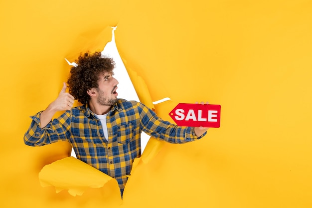 Vooraanzicht jonge man met rode verkoop schrijven op gele gescheurde achtergrond