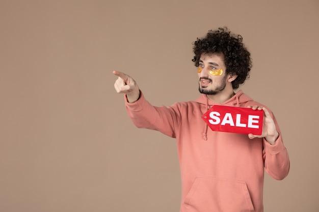 Vooraanzicht jonge man met rood verkoopnaambordje op bruine achtergrond gezichtssalon huid spa huidverzorging masseren winkelen