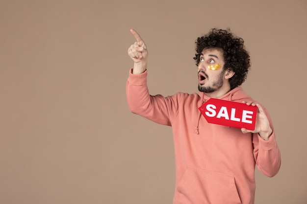 Vooraanzicht jonge man met rood verkoopnaambordje op bruine achtergrond gezichtssalon huid winkelen therapie spa huidverzorging masseren kleur