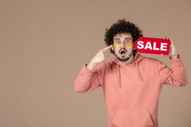 Vooraanzicht jonge man met rood verkoopnaambordje op bruine achtergrond gezichtssalon therapie huidverzorging masseren spa winkelen huid