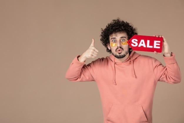 Vooraanzicht jonge man met rood verkoopnaambordje op bruine achtergrond gezichtssalon therapie masseren spa winkelen huid