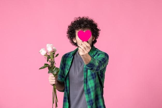Vooraanzicht jonge man met roze rozen en hartsticker op roze
