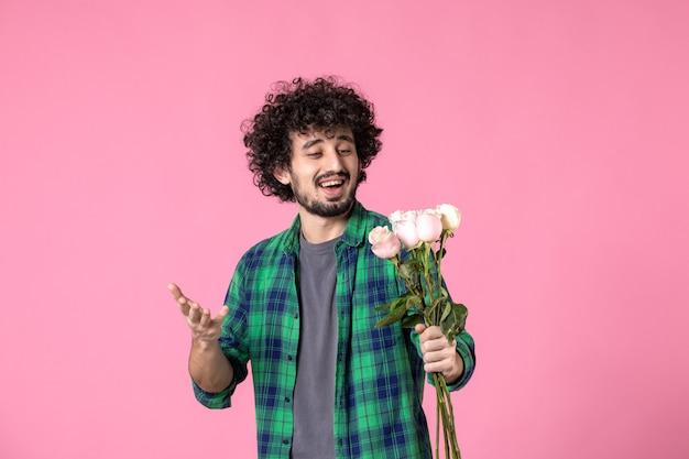 Vooraanzicht jonge man met roze rozen op roze kleur