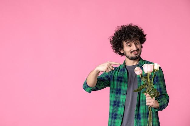 Vooraanzicht jonge man met roze rozen op roze
