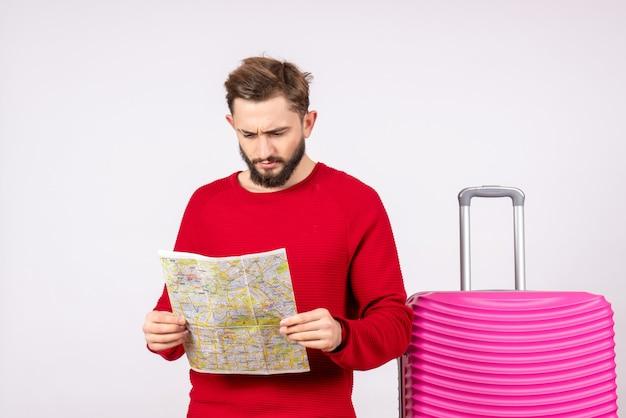 Vooraanzicht jonge man met roze tas en kaart op witte muur reis kleur vakantie vlucht reis zomertoerist te houden