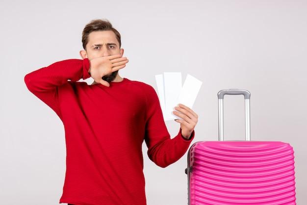 Vooraanzicht jonge man met roze tas en kaartjes houden op witte muur kleur reis vakantie vlucht reis toerist