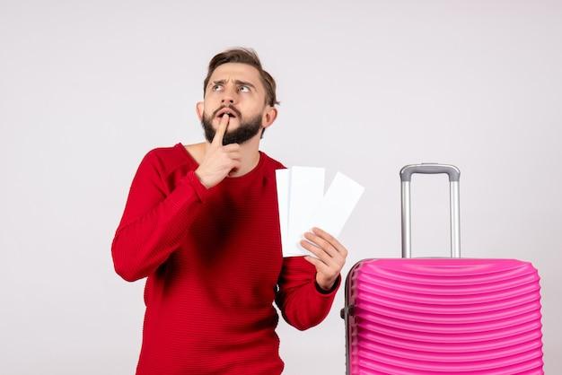 Vooraanzicht jonge man met roze tas en kaartjes houden op witte muur kleur reis vakantie vlucht reis zomer toerist