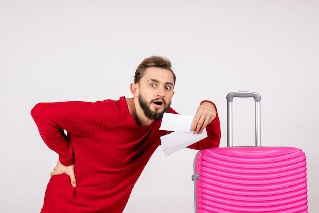 Vooraanzicht jonge man met roze tas en kaartjes houden op witte muur kleur reis vlucht reis toerist