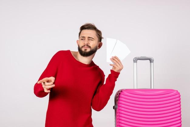 Vooraanzicht jonge man met roze tas en kaartjes houden op witte muur kleur reis vlucht reis toeristische vakantie