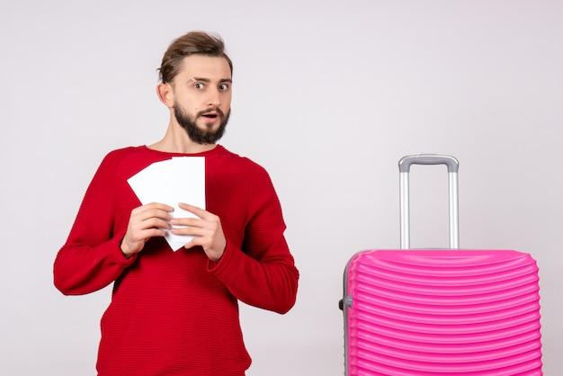 Vooraanzicht jonge man met roze tas en kaartjes houden op witte muur reis kleur vakantie vlucht reis toerist