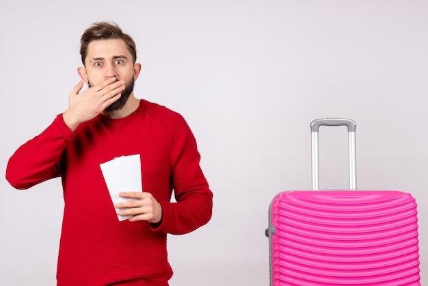 Vooraanzicht jonge man met roze tas en kaartjes houden op witte muur reis kleur vakantie vlucht reis zomer