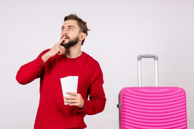 Vooraanzicht jonge man met roze tas en kaartjes houden op witte muur reis kleur vakantie vlucht reis zomertoerist