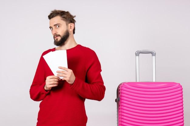 Vooraanzicht jonge man met roze tas en kaartjes houden op witte muur reis kleur vakantie vlucht zomertoerist