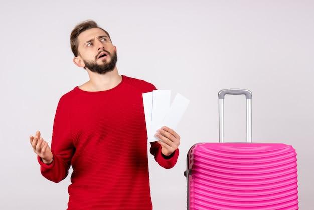 Vooraanzicht jonge man met roze tas en kaartjes houden op witte muur reis kleur vlucht reis zomertoerist