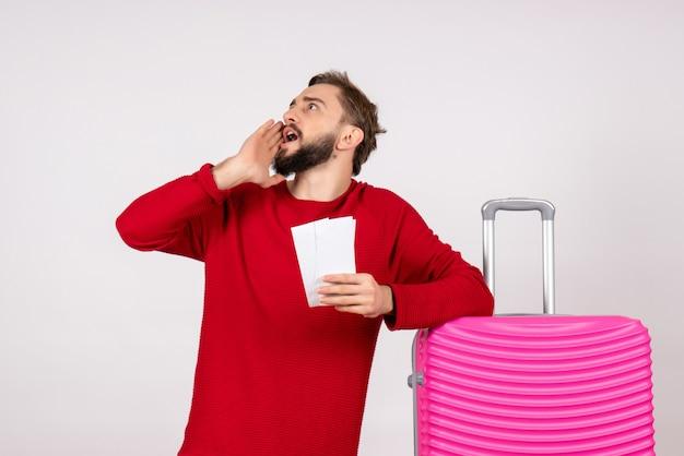 Vooraanzicht jonge man met roze tas en kaartjes houden op witte muur reis vlucht kleur reis toeristische vakantiefoto's