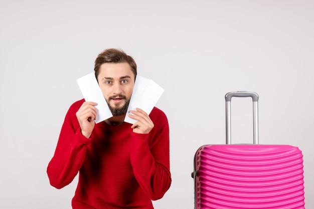 Vooraanzicht jonge man met roze tas en kaartjes houden op witte muur vlucht kleur reis reis toeristische vakantie