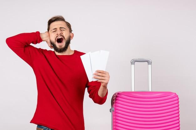 Vooraanzicht jonge man met roze tas en kaartjes houden op witte muur vlucht kleur reis toeristische vakantie foto emotie