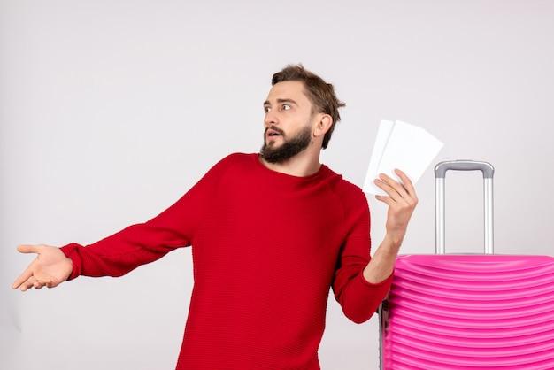 Vooraanzicht jonge man met roze tas en kaartjes op witte muur vluchten kleur reis reis toeristische vakantie te houden