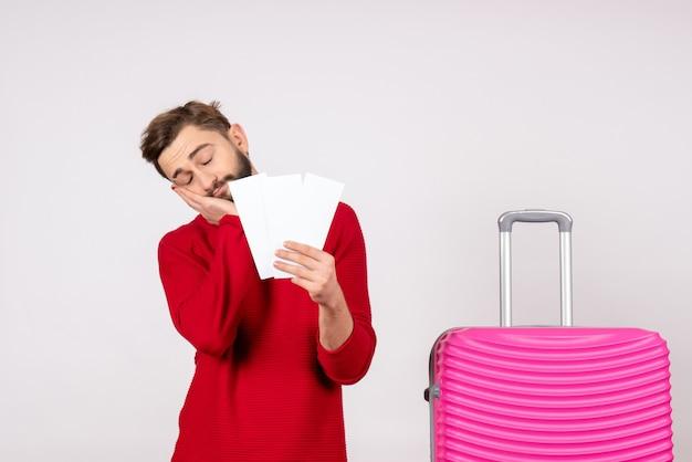 Vooraanzicht jonge man met roze tas en kaartjes vasthouden moe gevoel op witte muur reis vlucht kleur reis toeristische vakantie foto emotie