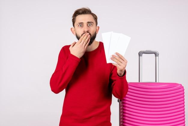 Vooraanzicht jonge man met roze tas en vliegtuigtickets op witte muur reis vlucht reis toeristische vakantie emotie foto's te houden