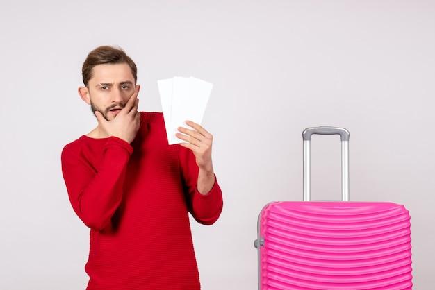Vooraanzicht jonge man met roze tas en vliegtuigtickets op witte muur reis vlucht reis toeristische vakantie emotie foto te houden